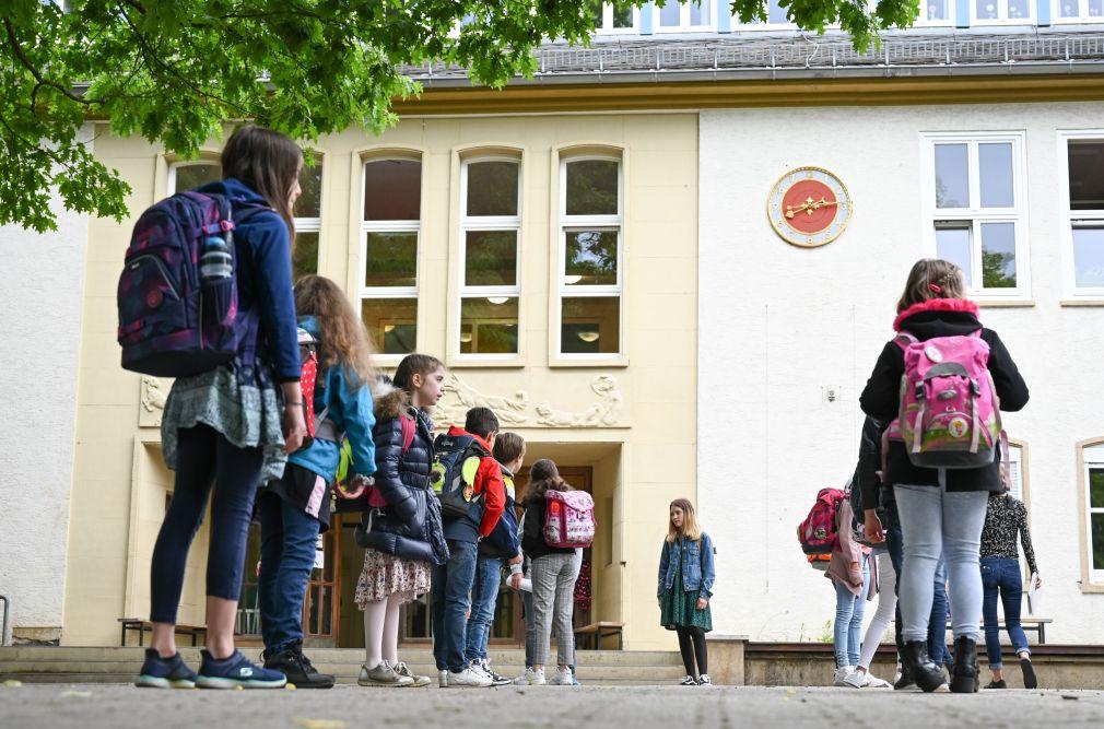 Vier Schüler stehen vor dem Eingang der Schule in einer Schlange.