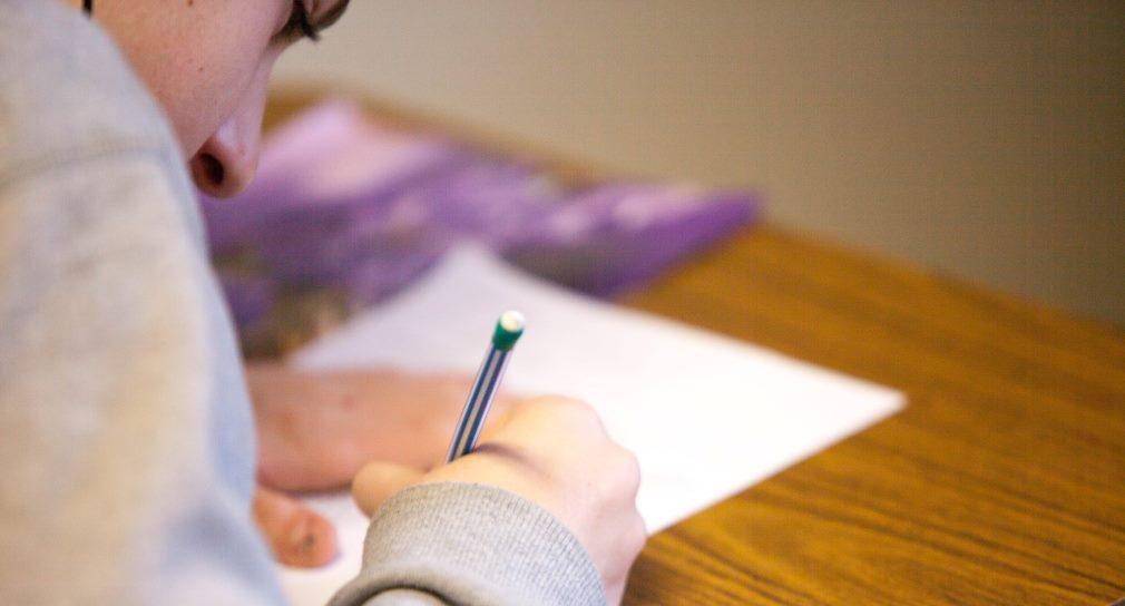 Der Betrachter blickt über die Schulter eines Jungen, der einen Stift in der Hand hält und auf ein Blatt Papier schreibt.