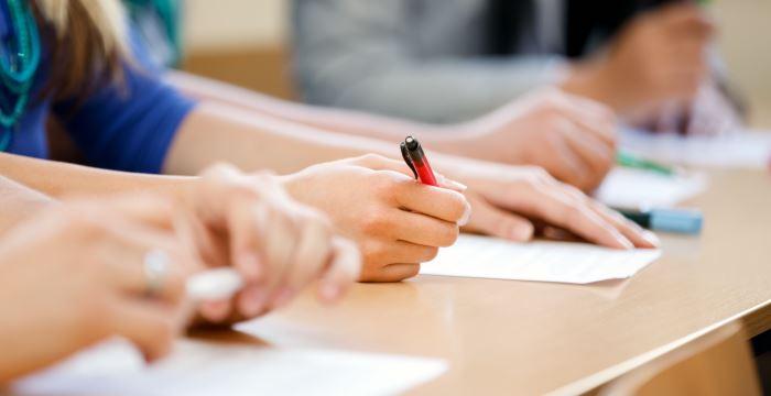 Schüler mit Stift und Blatt an einem Tisch